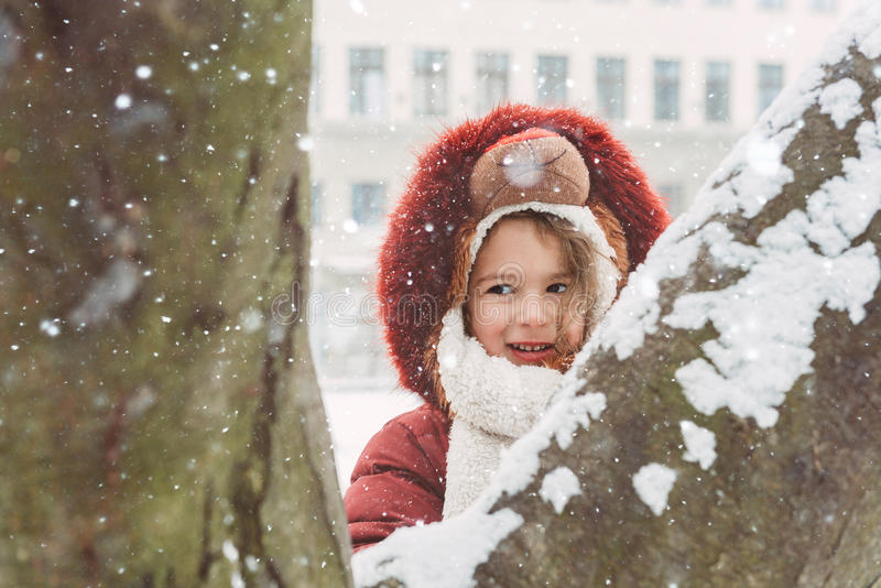 Positive little girl. Portrait of little girl outdoor during snow storm,selective focus royalty free stock photo