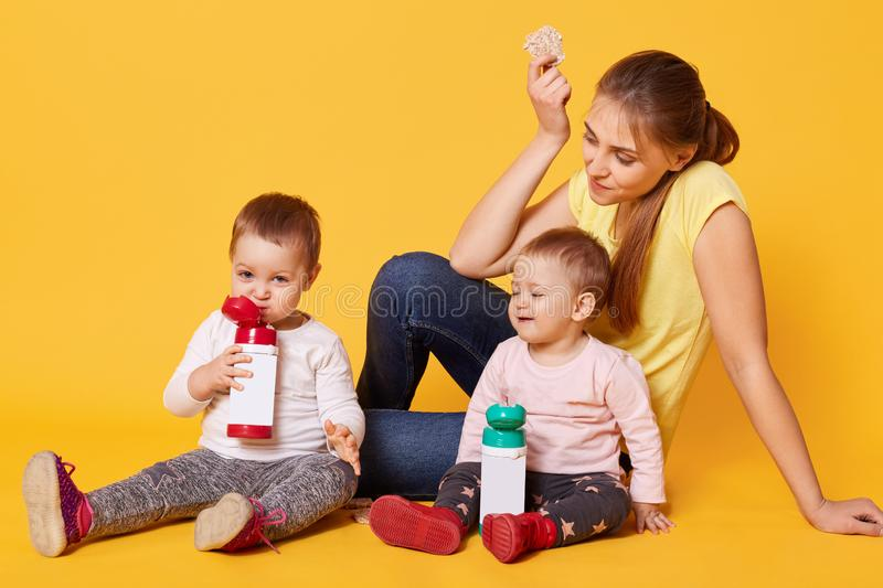 A positive loving mom cares her twin daughters, sits on the floor, being happy to spend time with little babies. Cheerful merry stock photo