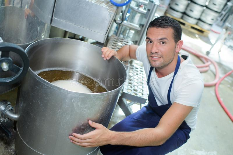 Positive male brewery worker on beer production factory stock image