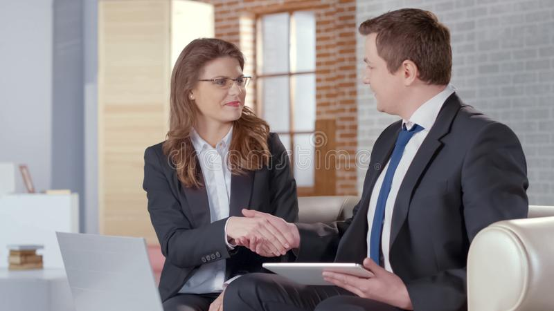 Positive male and female business partners shaking hands, successful agreement stock images