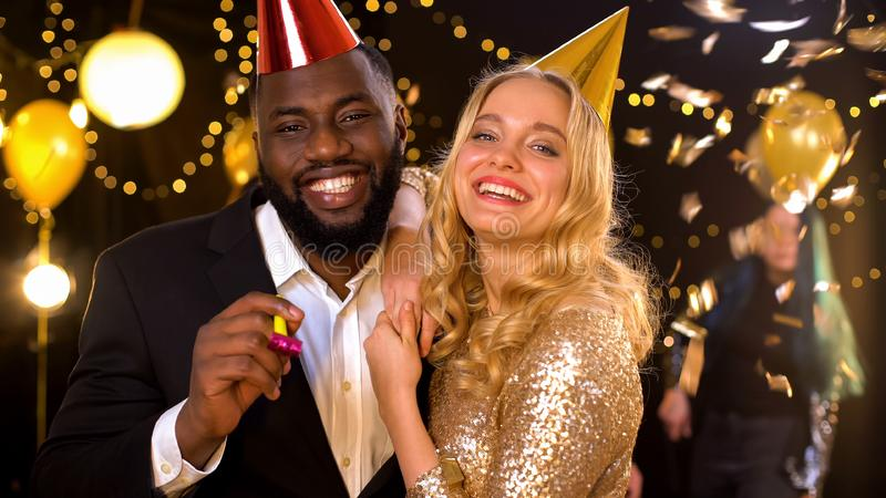 Positive male and female friends celebrating new year night club, blowing horn stock images