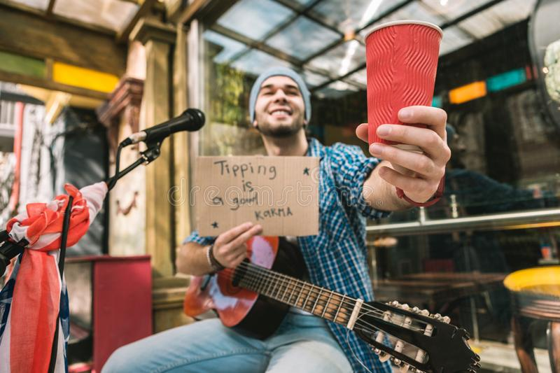 Positive male musician believing in reward for play stock image