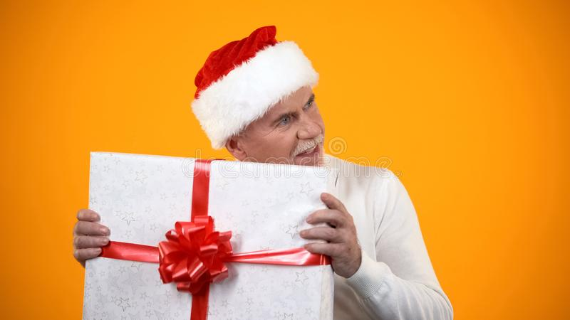 Positive male pensioner in santa claus hat shaking giftbox and smiling, surprise stock images