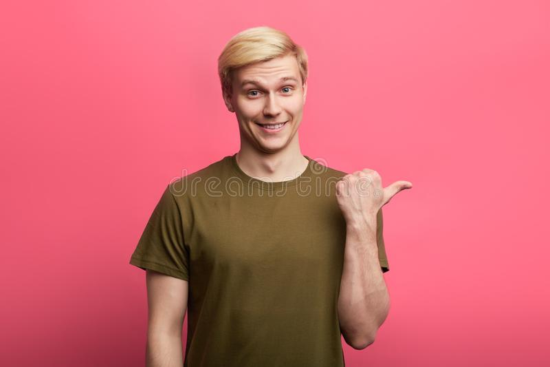 Positive man looking at the camera and pointing to the side with thumb up. stock images
