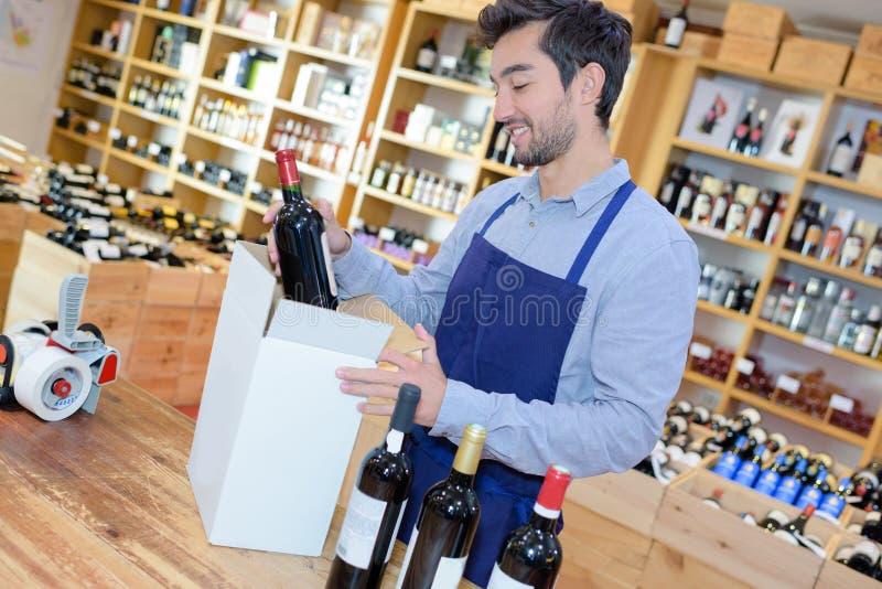 Positive man seller wearing uniform having bottle wine stock photography