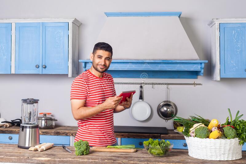 Positive man standing in modern kitchen holding tablet pc and looking at camera with smile, searching food recipe on internet,. Reading calories, basket of stock image