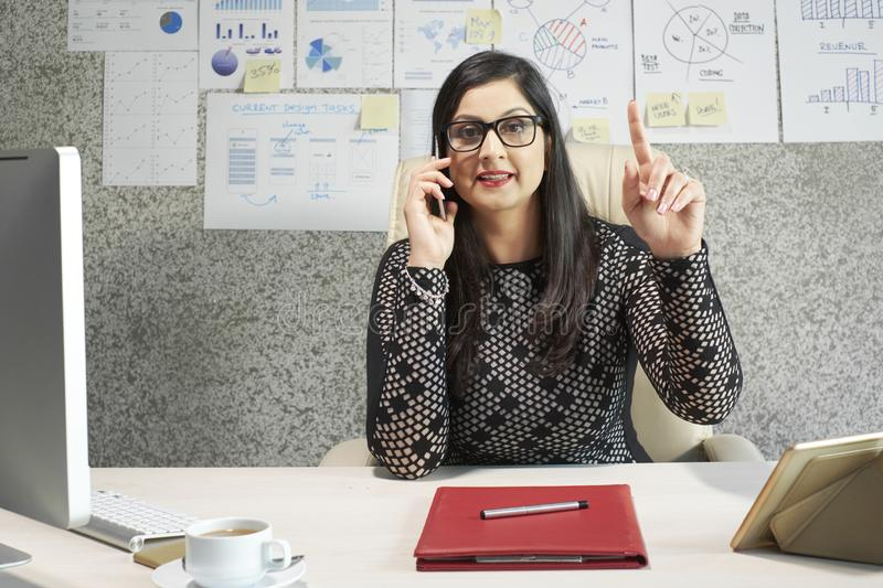 Business lady talking on phone. Positive mature Indian busiensswoman talking on phone and explaining information her customer stock images