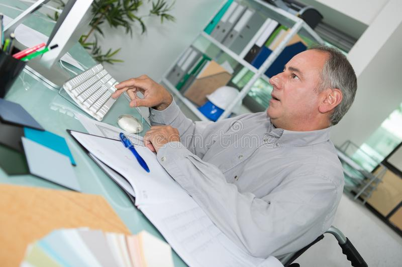 Positive mature man working with computer in office royalty free stock images