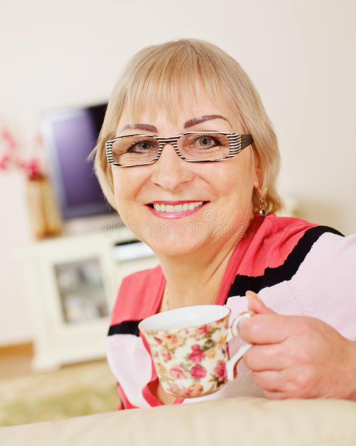Positive mature woman on sofa with mug royalty free stock photos