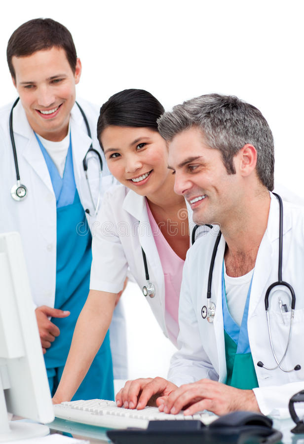 Positive medical team working at a computer. Against a white background royalty free stock photo