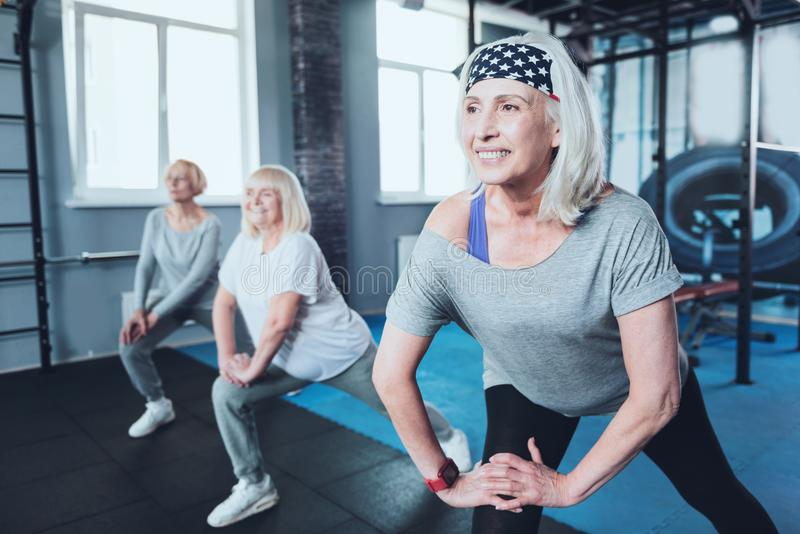Positive minded elderly ladies doing warmup at fitness club royalty free stock photos
