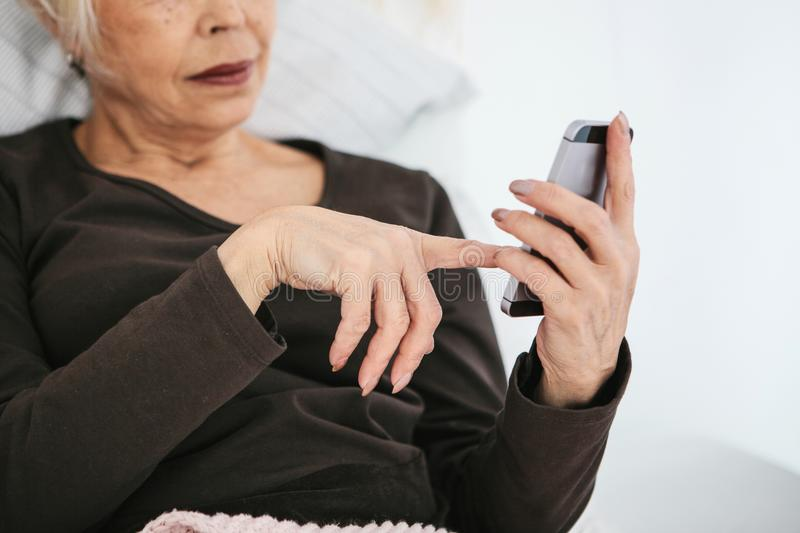 A positive modern elderly woman is holding a cell phone and is using it. The older generation and modern technology. A positive modern elderly woman is holding royalty free stock photography