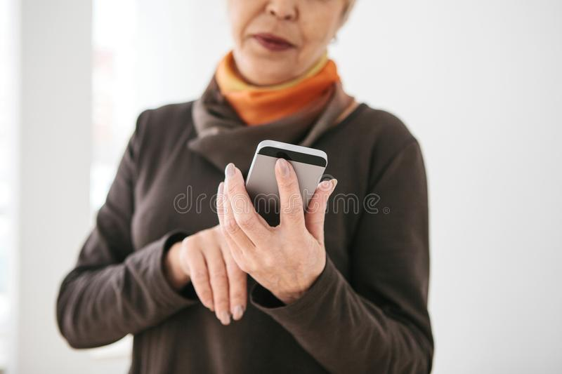 A positive modern elderly woman is holding a cell phone and is using it. The older generation and modern technology. royalty free stock photography