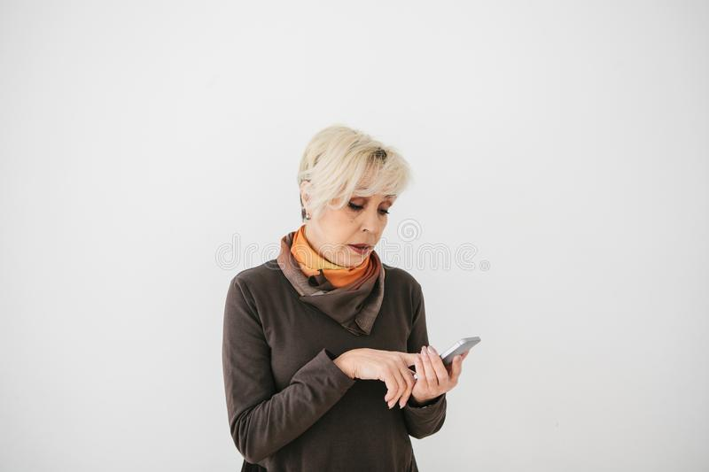 A positive modern elderly woman is holding a cell phone and is using it. The older generation and modern technology. stock photos