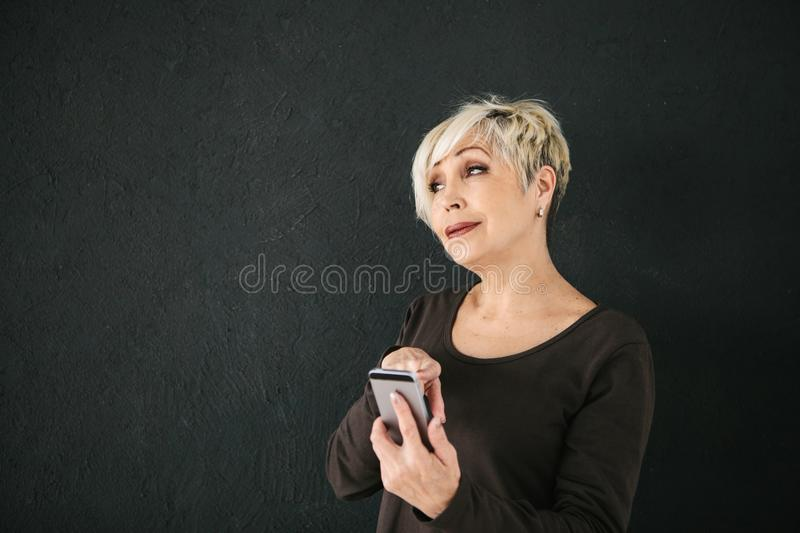 A positive modern elderly woman is holding a cell phone and is using it. The older generation and modern technology. stock images