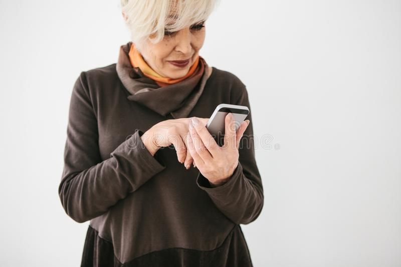 A positive modern elderly woman is holding a cell phone and is using it. The older generation and modern technology. stock image