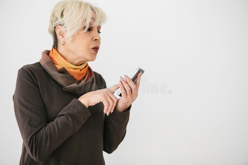 A positive modern elderly woman is holding a cell phone and is using it. The older generation and modern technology. royalty free stock photos