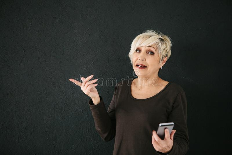 A positive modern elderly woman is holding a cell phone and is using it. The older generation and modern technology. stock photo