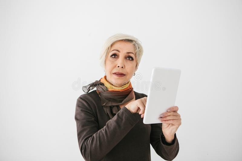 A positive modern elderly woman holds a tablet in her hands and uses it. The older generation and modern technology. stock photos