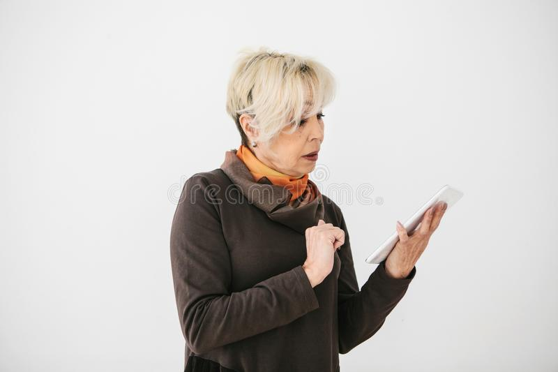 A positive modern elderly woman holds a tablet in her hands and uses it. The older generation and modern technology. stock photo