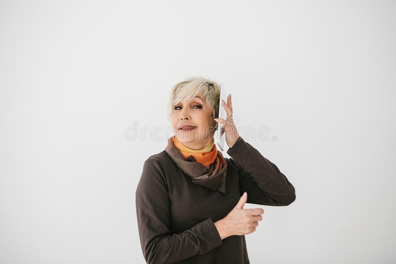 A positive modern elderly woman holds a tablet in her hands and uses it. The older generation and modern technology. A positive modern elderly woman holds a stock photography