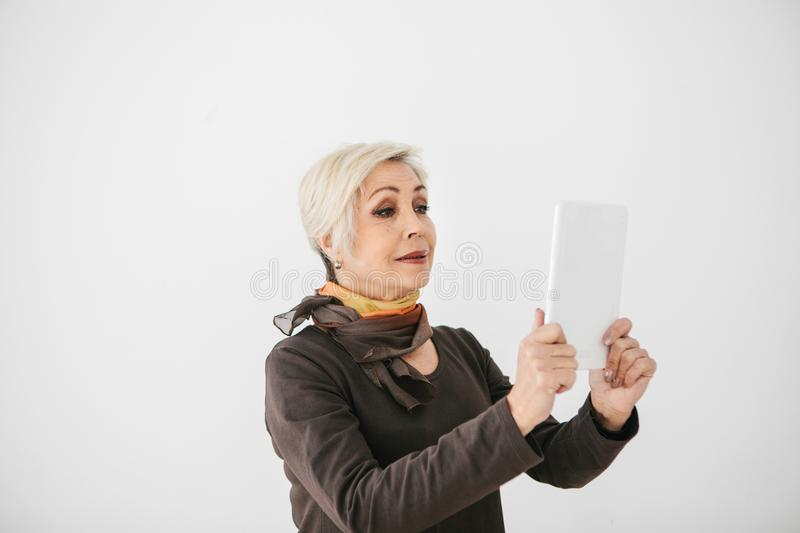 A positive modern elderly woman holds a tablet in her hands and uses it. The older generation and modern technology. A positive modern elderly woman holds a royalty free stock image