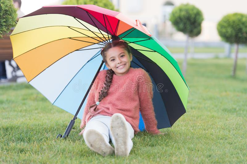 Positive mood in autumn rainy weather. Little girl under colorful umbrella. Rainbow after rain. Multicolored umbrella. For little happy girl. Optimist and stock photo