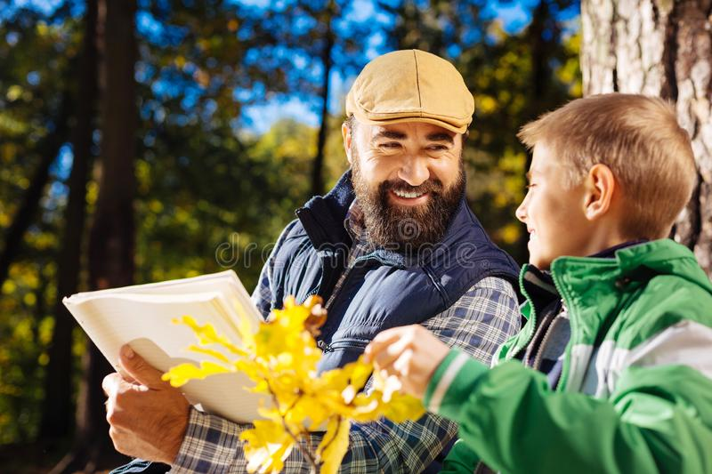 Cheerful bearded man smiling to his son royalty free stock image