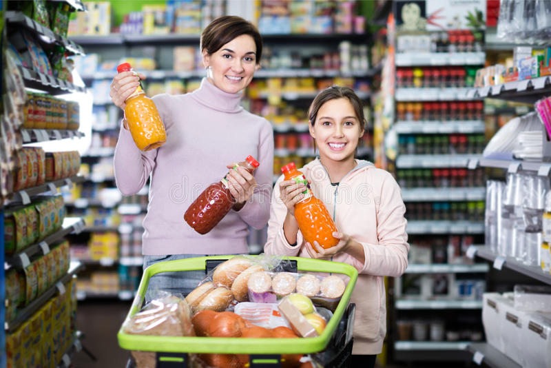 Positive mother with daughter choosing refreshing beverages in s stock images