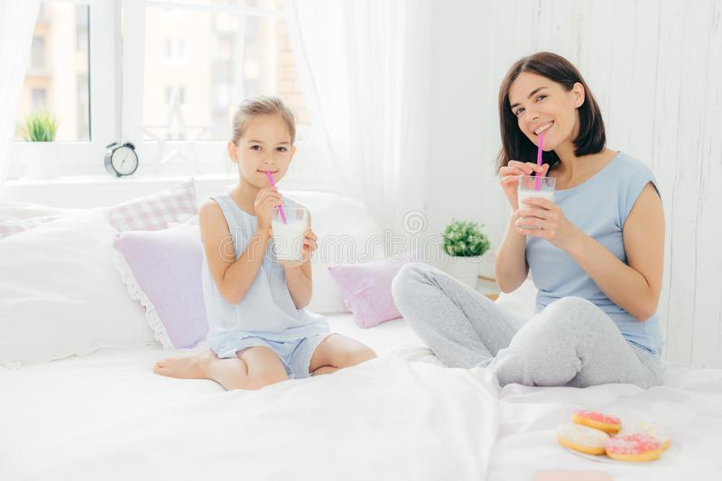Positive mother and daughter start their day with delicious breakfast, drink cocktail with tasty sweet doughnuts, sits on white be stock photography