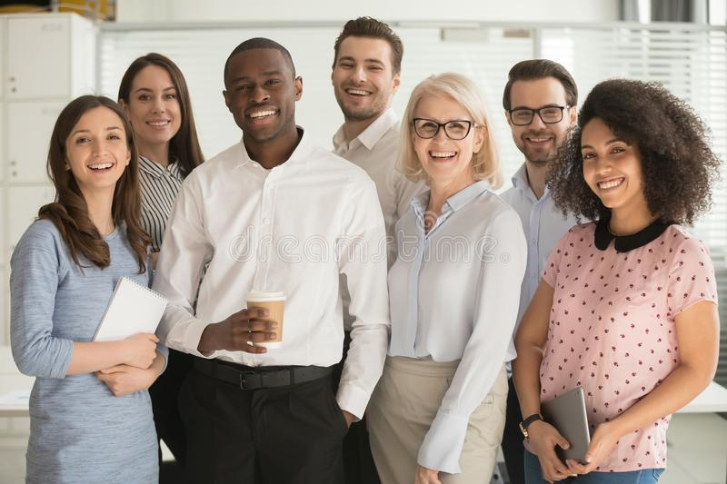 Positive multi racial corporate team posing looking at camera. Motivated international multi-ethnic company members aged and young corporate team photographing royalty free stock photos