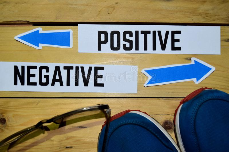 Positive or Negative opposite direction signs with sneakers and eyeglasses on wooden. Vintage background. Business and education concepts royalty free stock images