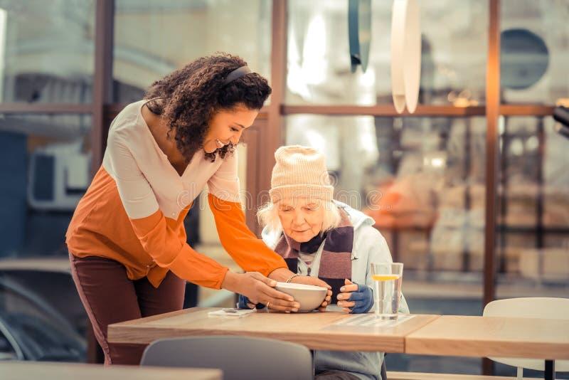 Positive nette Frau, die auf dem Tisch eine Schüssel mit Suppe setzt lizenzfreie stockfotografie