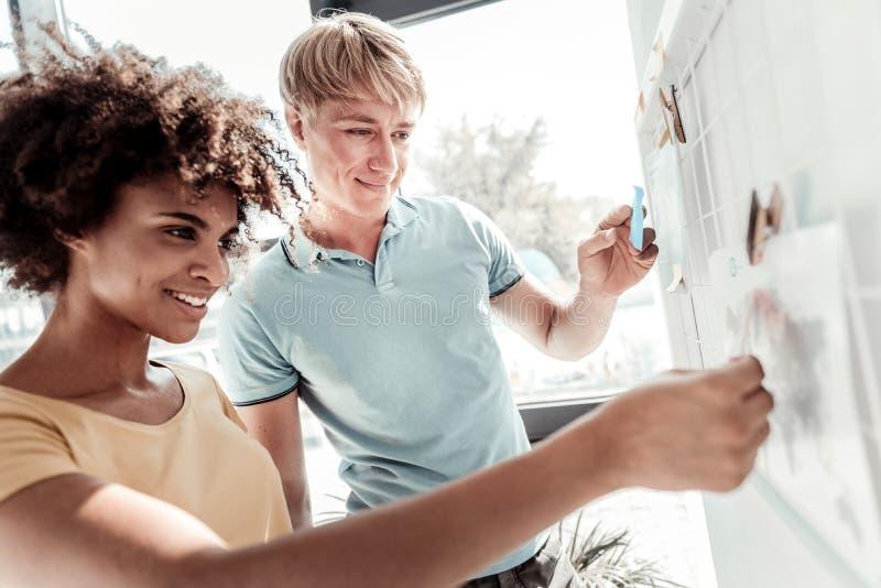 Positive nette Leute, die das whiteboard betrachten lizenzfreie stockbilder