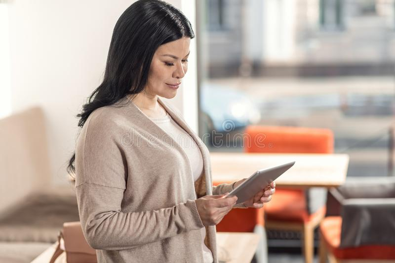 Positive nice woman standing in the cafeteria. Portable device. Positive nice pleasant woman standing in the cafeteria and holding a tablet while looking at it royalty free stock photos