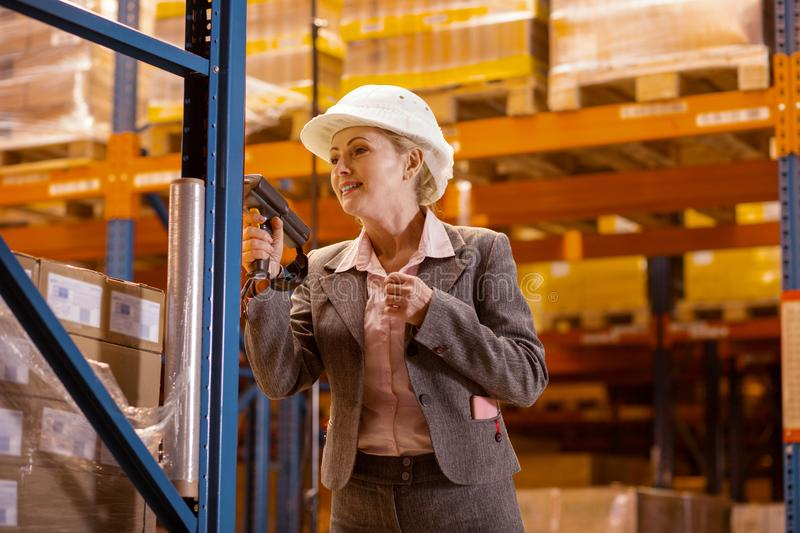 Positive nice woman using a scanning device. Warehouse manager. Positive nice woman using a scanning device while working as a warehouse manager stock photography