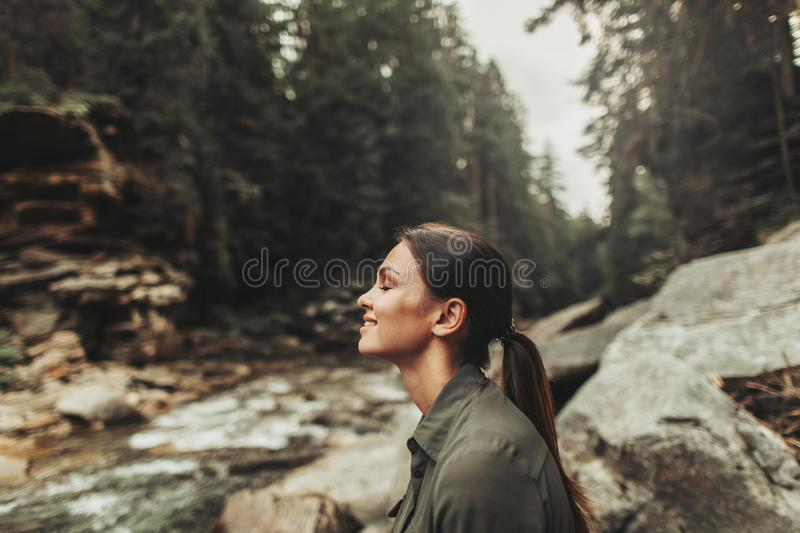 Pleased young woman enjoying fresh air in the forest stock photo