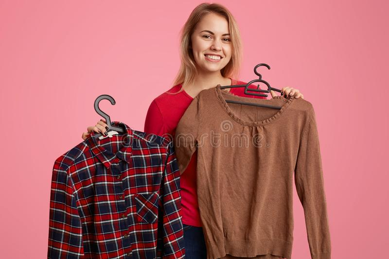 Positive optimistic woman with light hair, toothy smile, holds new clothes on hangers, rejoices successful purchases, looks royalty free stock image