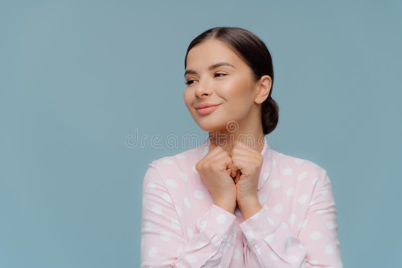 Positive optimistische Dame hält Fäuste zusammen gedrückt unter Kinn, schaut gladfully beiseite, trägt Tupfenhemd, schaut beiseit stockbild