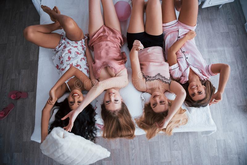Positive people. Inverted portrait of charming girls that lying on bed in nightwear. Top view stock photos