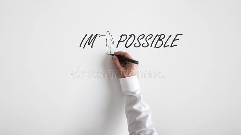 Positive personal attitude concept. Male hand drawing a shape of a person to push away letters IM from the word impossible over white background with plenty of royalty free stock photos