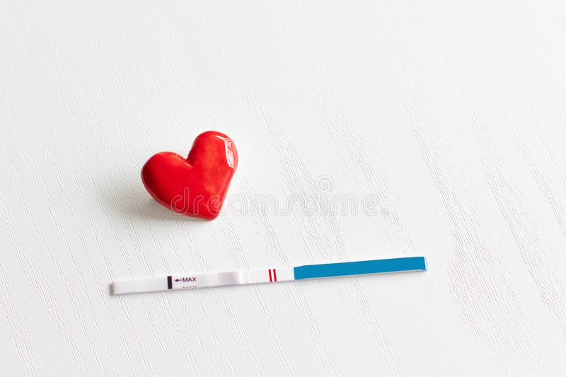 Positive pregnancy test and a heart stock photography