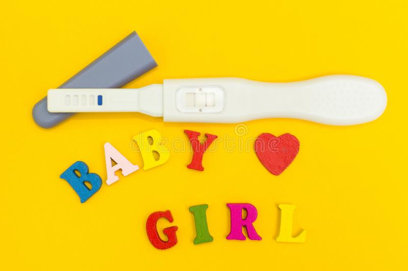 Positive pregnancy test, heart and the word `baby and girl` on a yellow background. Positive pregnancy test, heart and the word `baby and girl` on a yellow royalty free stock image