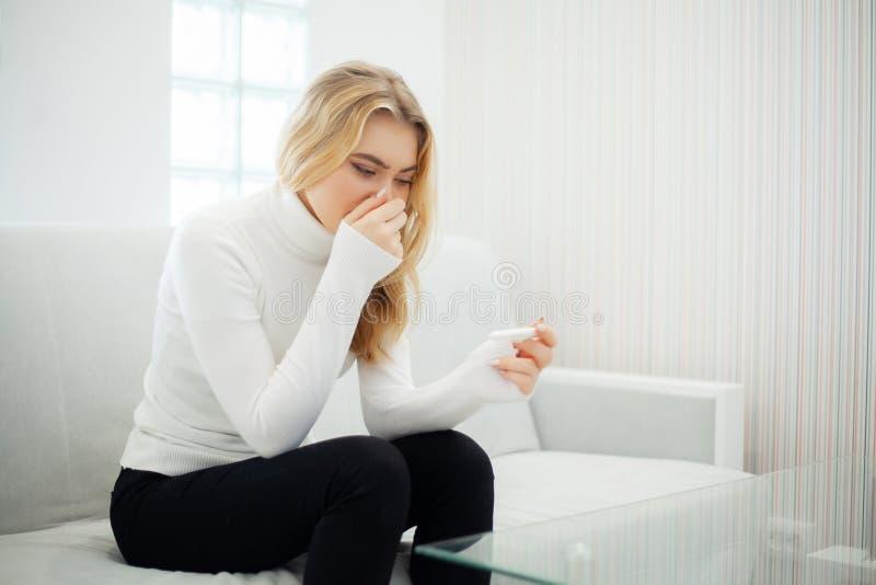 Positive pregnancy test. Portrait of desperate young woman holding pregnancy test stick stock photos