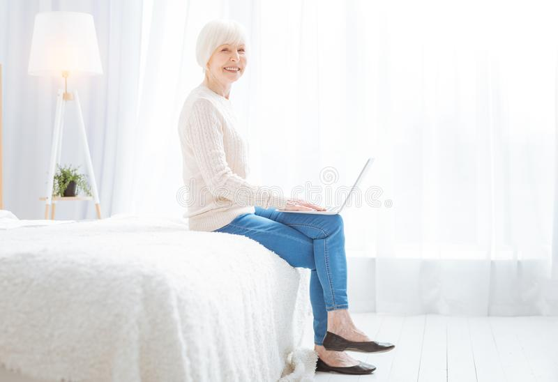 Positive progressive pensioner smiling while enjoying modern technologies. Smart pensioner. Clever progressive aged woman looking happy while sitting in her royalty free stock photography
