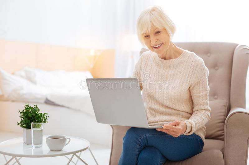 Positive progressive pensioner using a modern laptop and feeling happy. Wonderful device. Cheerful kind progressive aged woman feeling excited and happy while stock photography