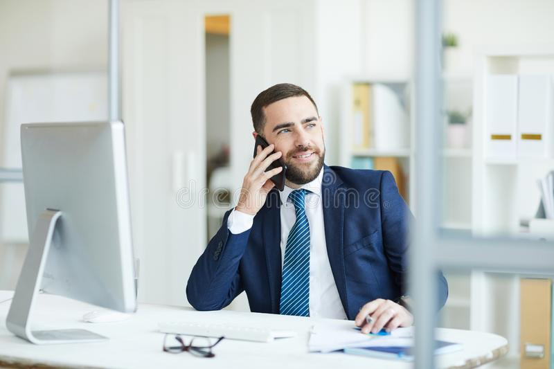 Positive project manager discussing plans on phone stock photo