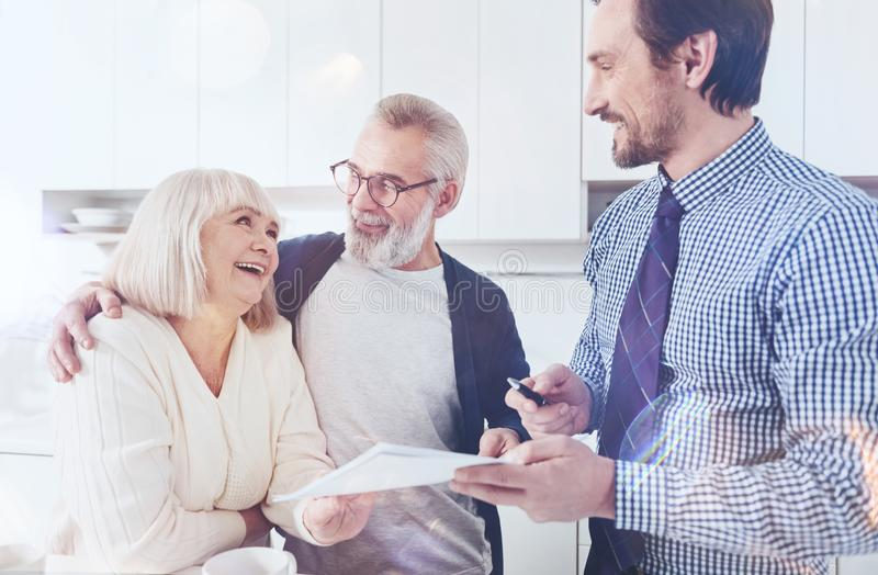 Positive real estate agent talking with elderly couple royalty free stock photo