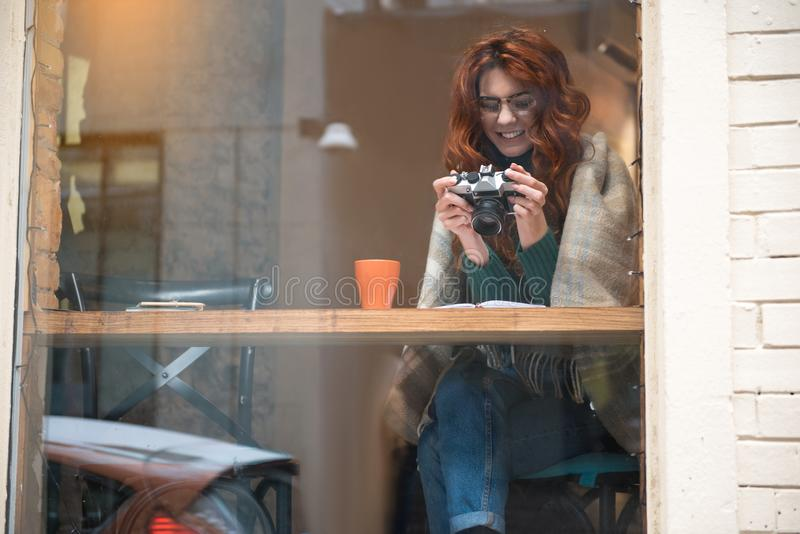 Positive red-haired girl looking at photographs on camera screen stock photos