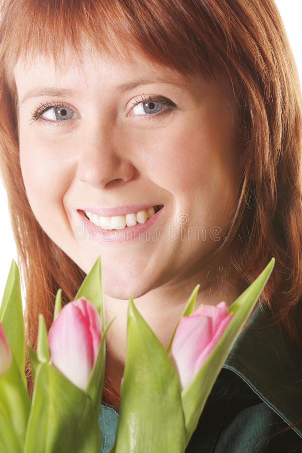 Positive redhead with pink tulips royalty free stock photo